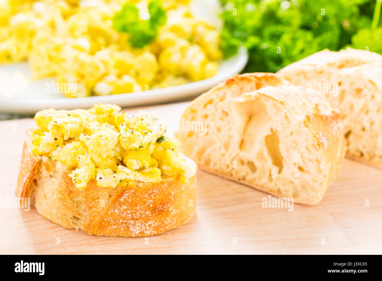 scrambled eggs with chive, herbs and baguette - Stock Image