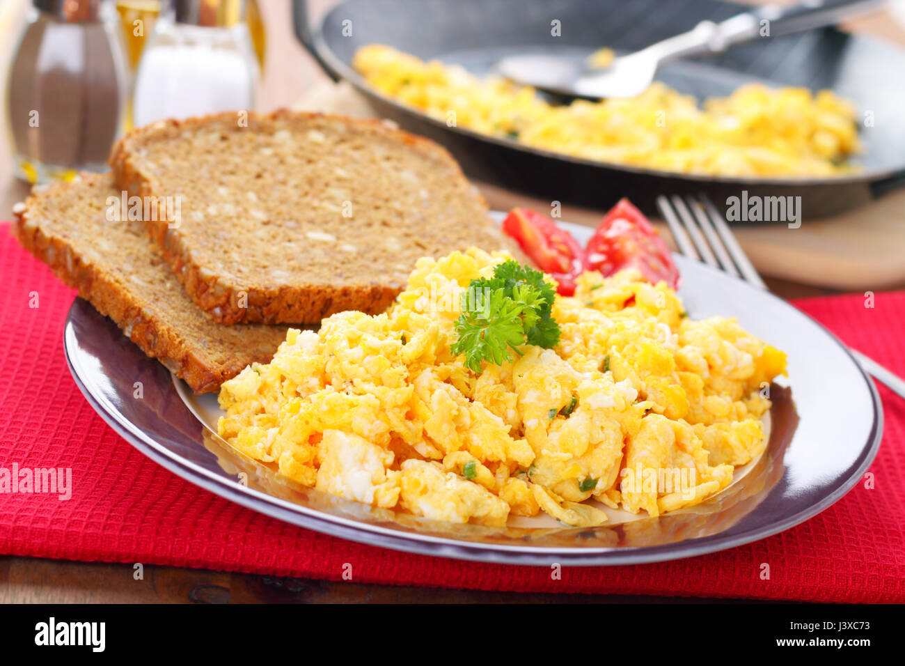 scrambled eggs with chives and herbs and two slices of bread - Stock Image