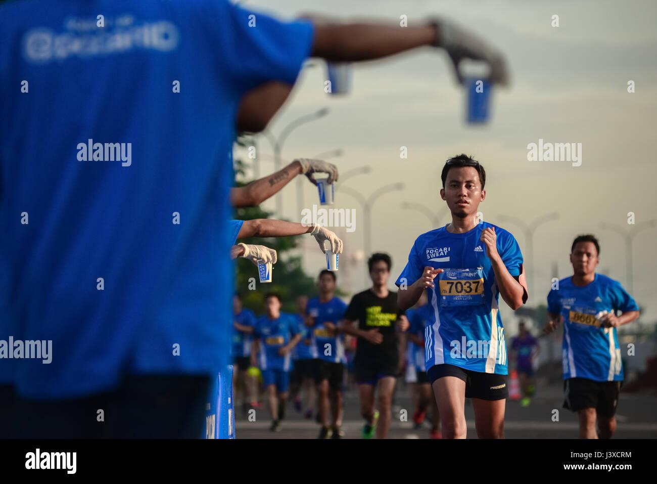 Runners pass a water station during the 2015 Pocari Run in South Tangerang, Banten, Indonesia. © Reynold Sumayku - Stock Image