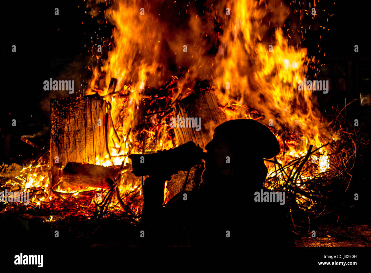 silhouette of a woman drinking from a bottle with background of sparks and tongues of bonfire - Stock Image