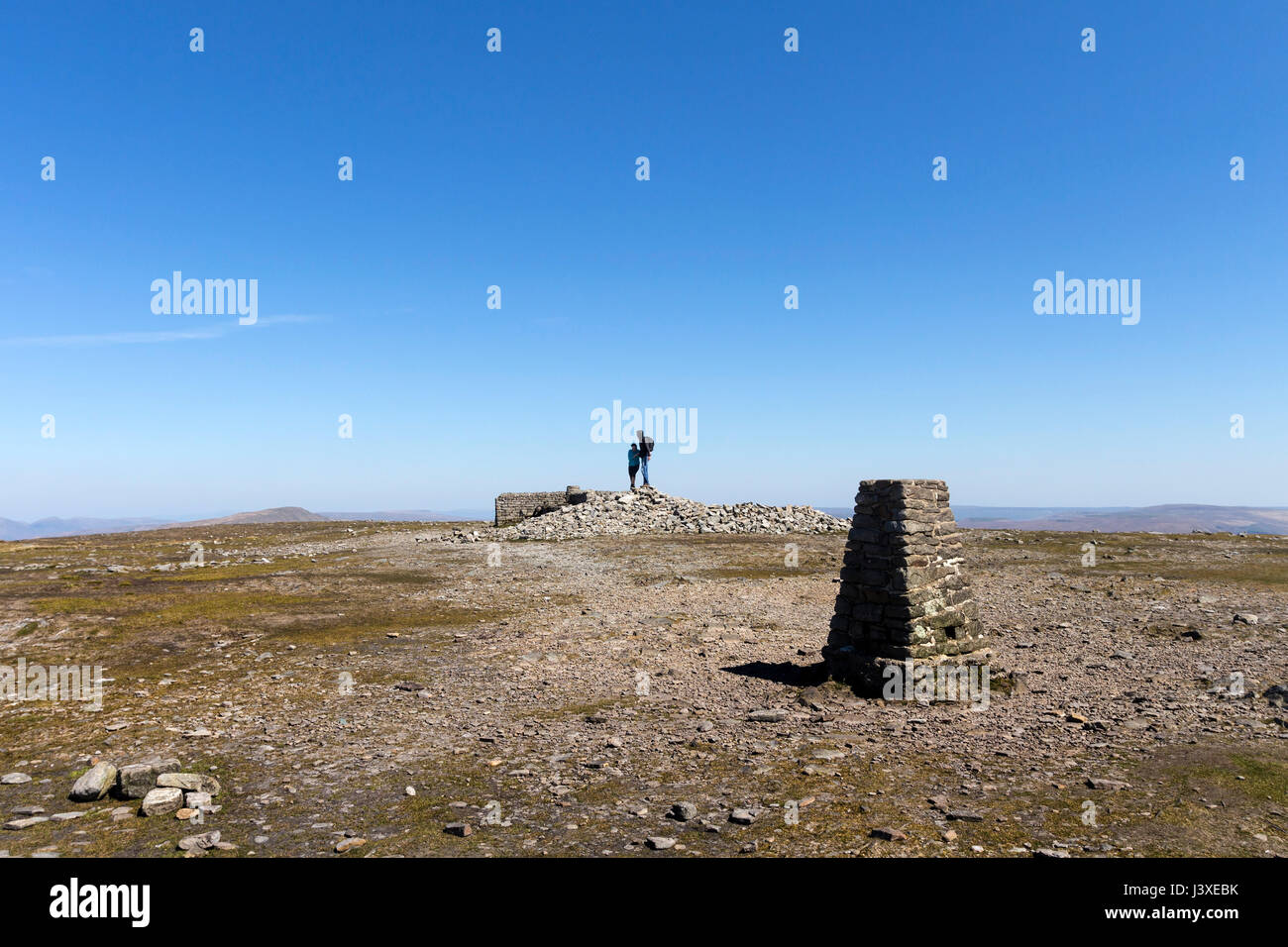 Walkers Standing on the Summit of Ingleborough under a Blue Sky, Yorkshire Dales, UK - Stock Image