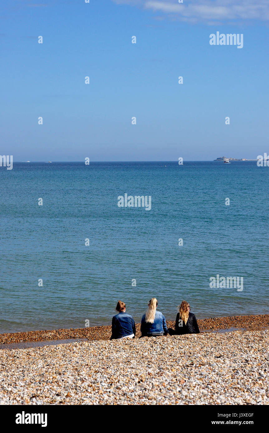 Three girls sitting on a beach looking out to sea - pebbles blue sea and sky - ship on the horizon - wishful thinking - Stock Image