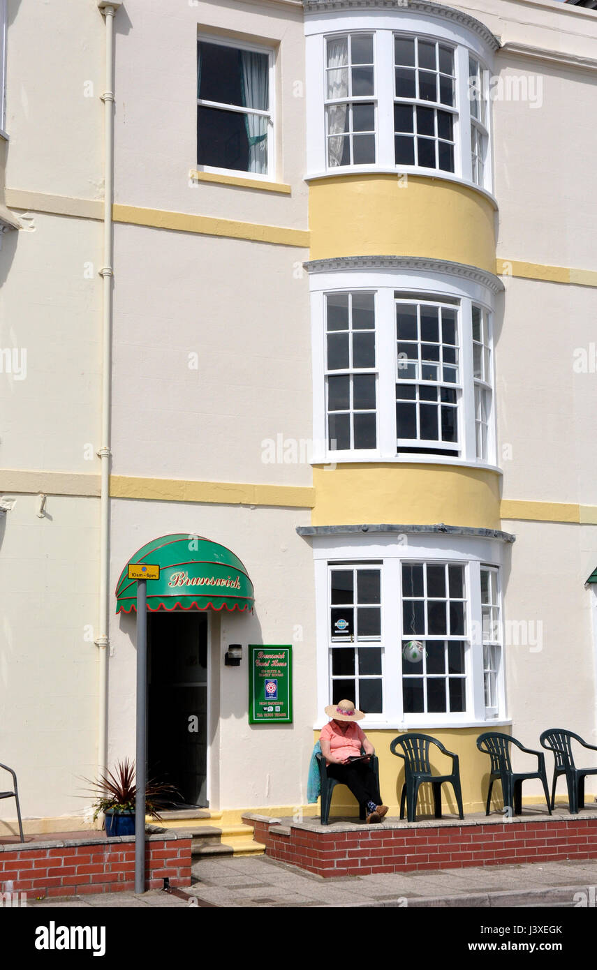 Small period hotel seafront Weymouth Dorset - resident sitting outside reading - enjoying sunshine- bow windows - Stock Image