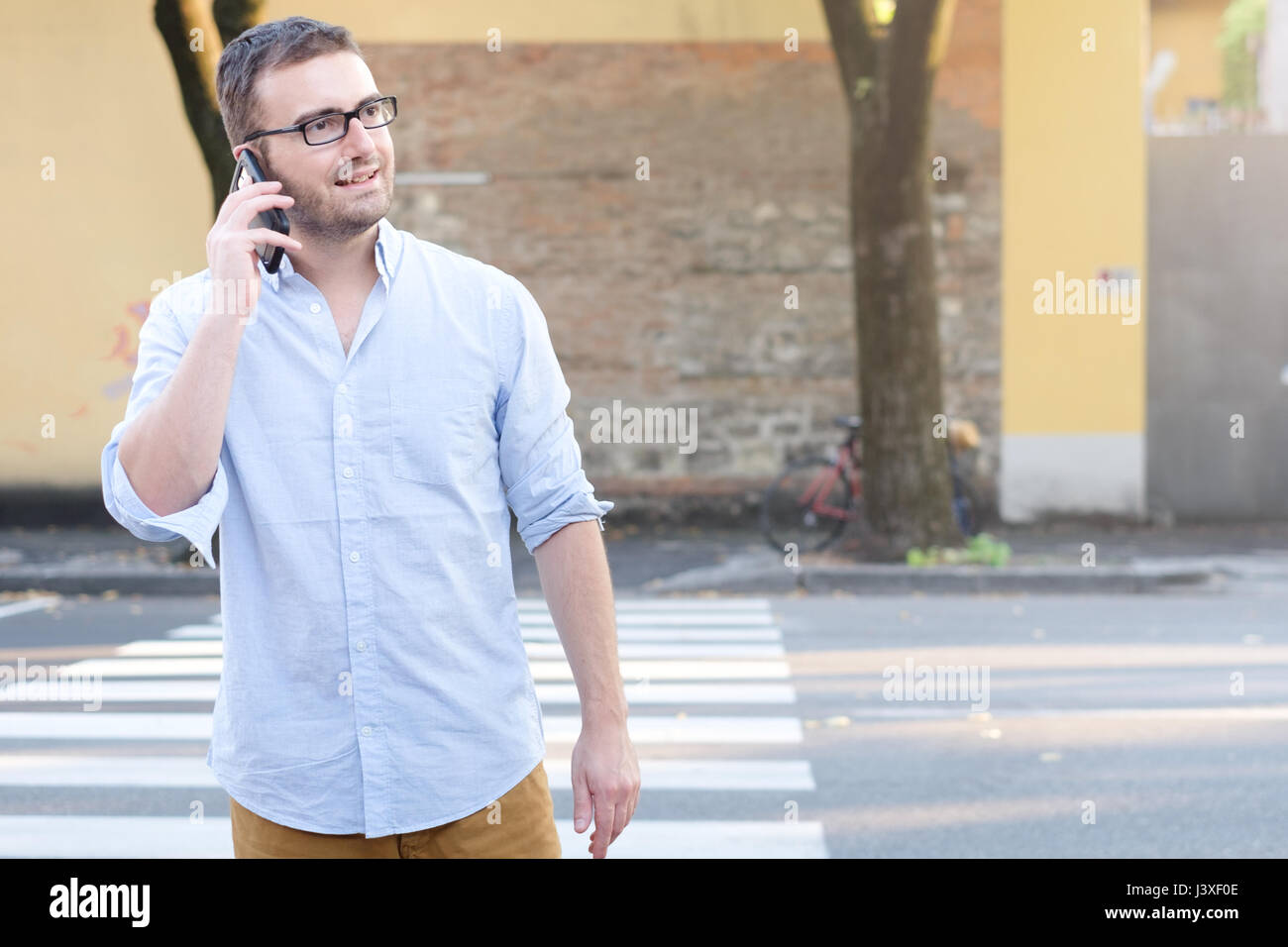 Man calling on his smartphone and walking in the city streets - Stock Image