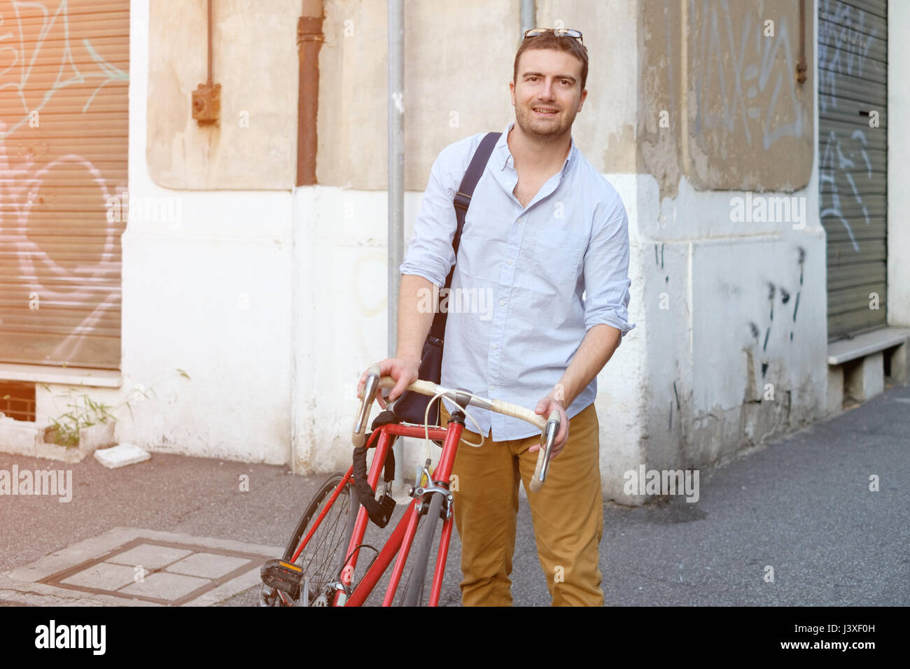 Fashionable man holding his bike in the city street - Stock Image