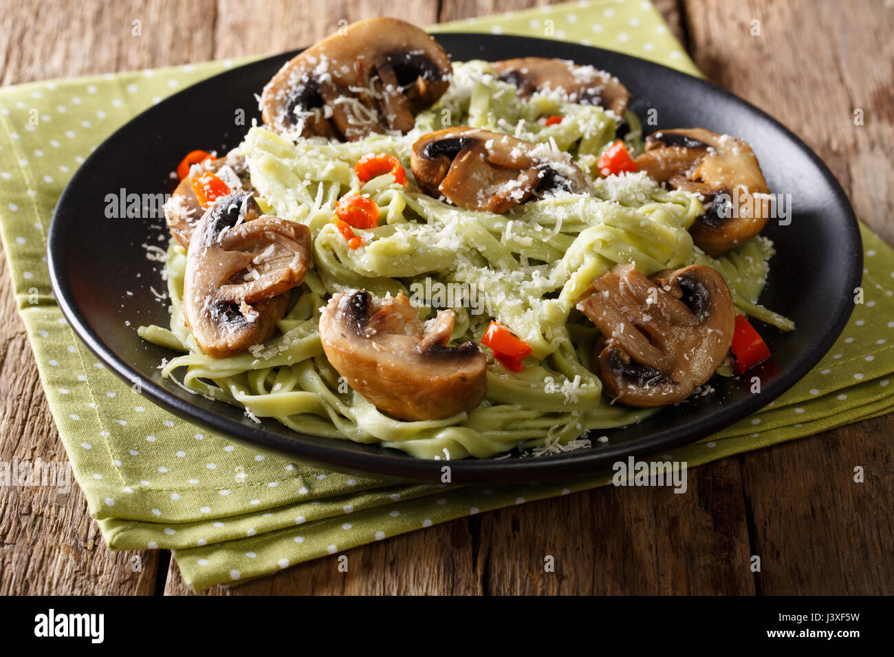 Homemade spinach pasta with fried mushrooms, chili pepper and cheese close-up on a plate. horizontal Stock Photo