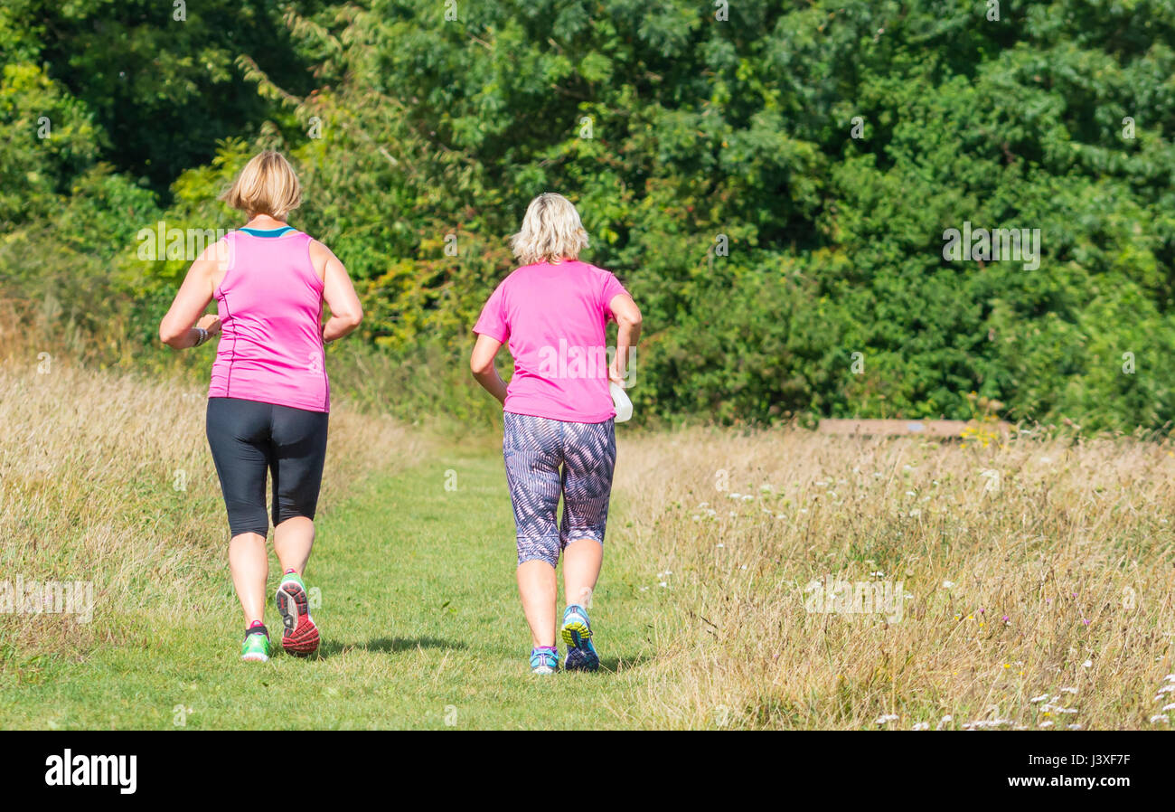 Pair of female joggers jogging through fields in the British countryside. Exercising concept. Keeping fit concept. - Stock Image