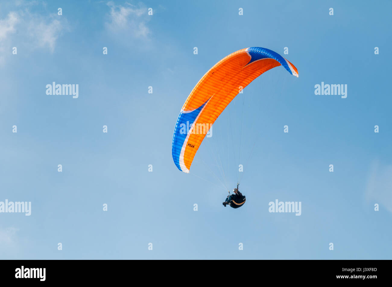 LAKE DISTRICT, UNITED KINGDOM - MAY 22, 2010: A paraglider is flying against a blue sky enjoying the wonderful day Stock Photo