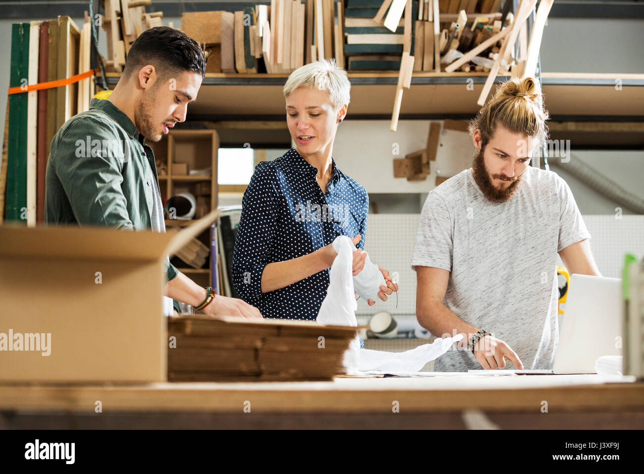 3 young people packing up products in a small warehouse Stock Photo