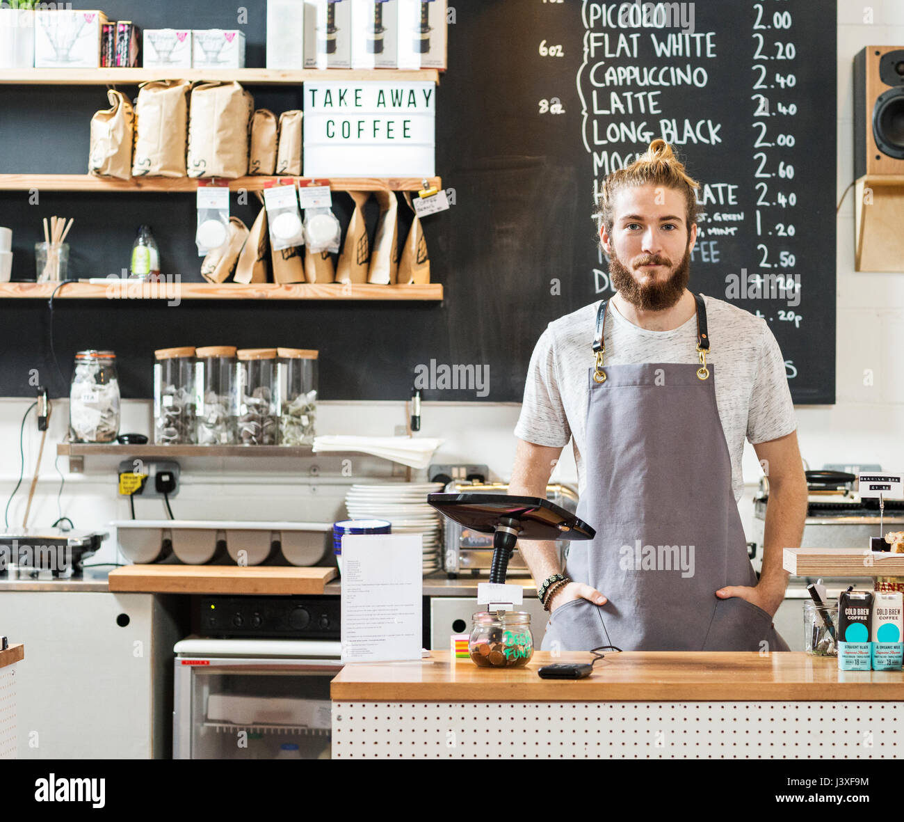 Portrait of a young man behind a counter in a cafe - Stock Image