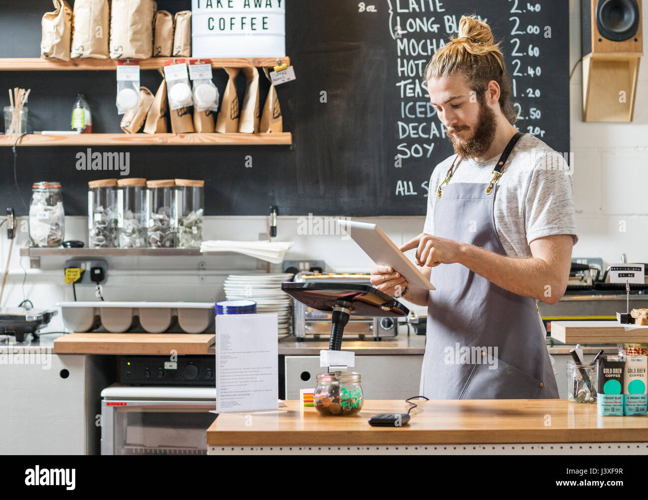 young man behind a counter in a cafe using a tablet - Stock Image