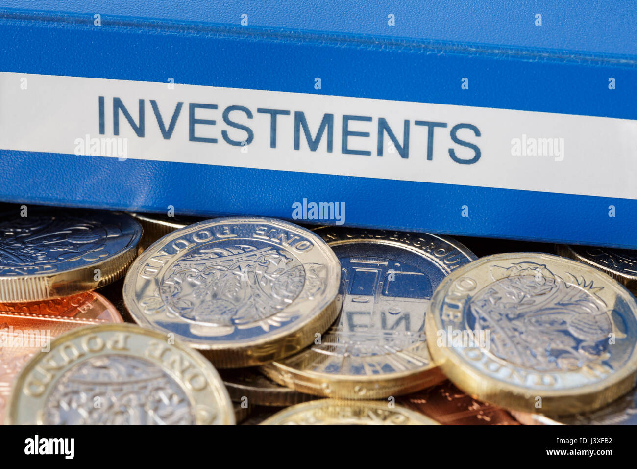 Investments portfolio on English pounds £ sterling money new pound coins GBP cash to illustrate investing and saving Stock Photo