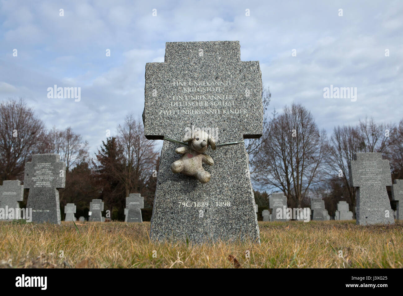 Toy dog fixed to the grave of two unknown children who died during World War II on the ground of the German War - Stock Image