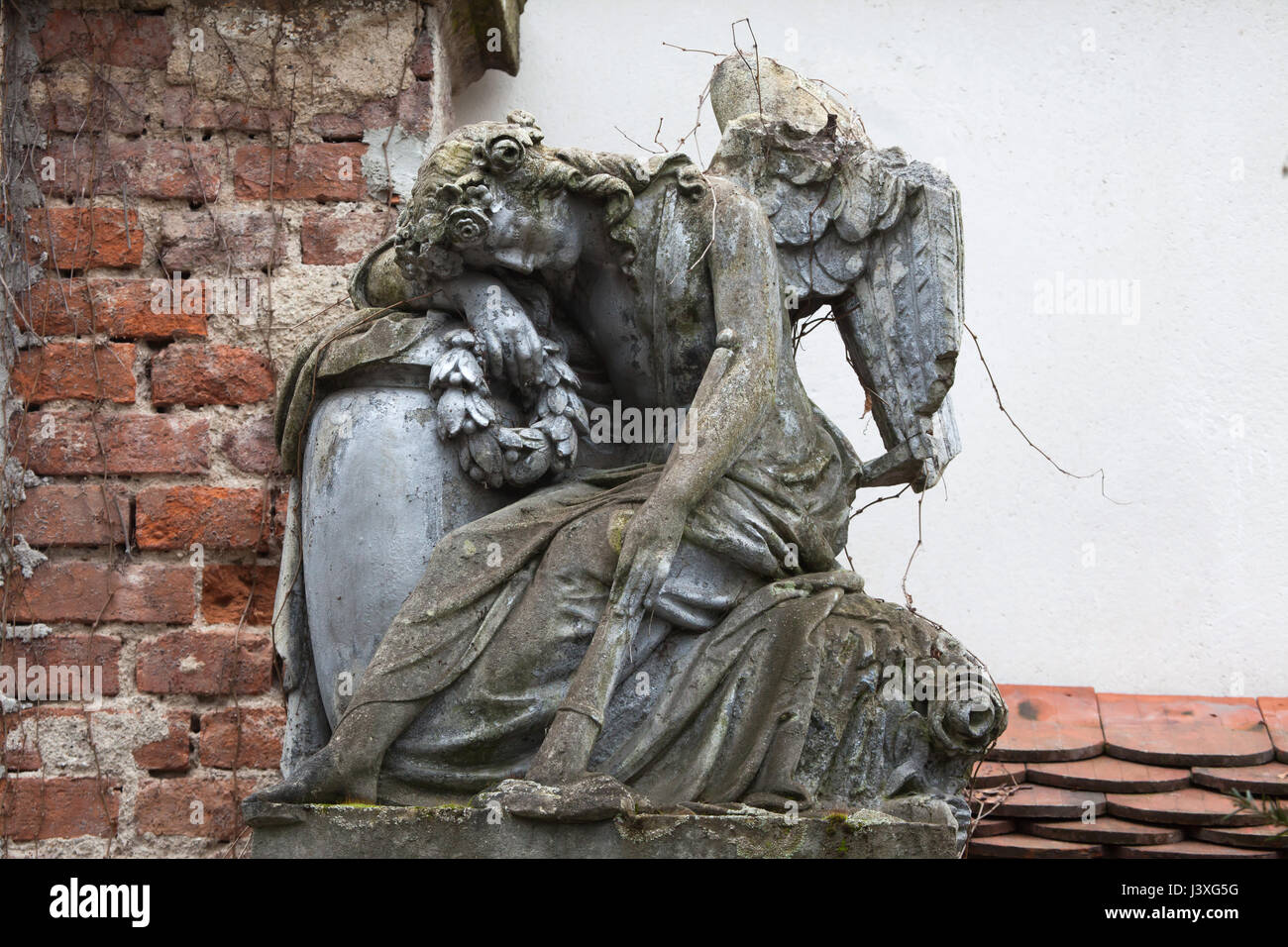 Statue of a mourning angel on an abandoned grave at the Central Cemetery in Brno, Czech Republic. - Stock Image