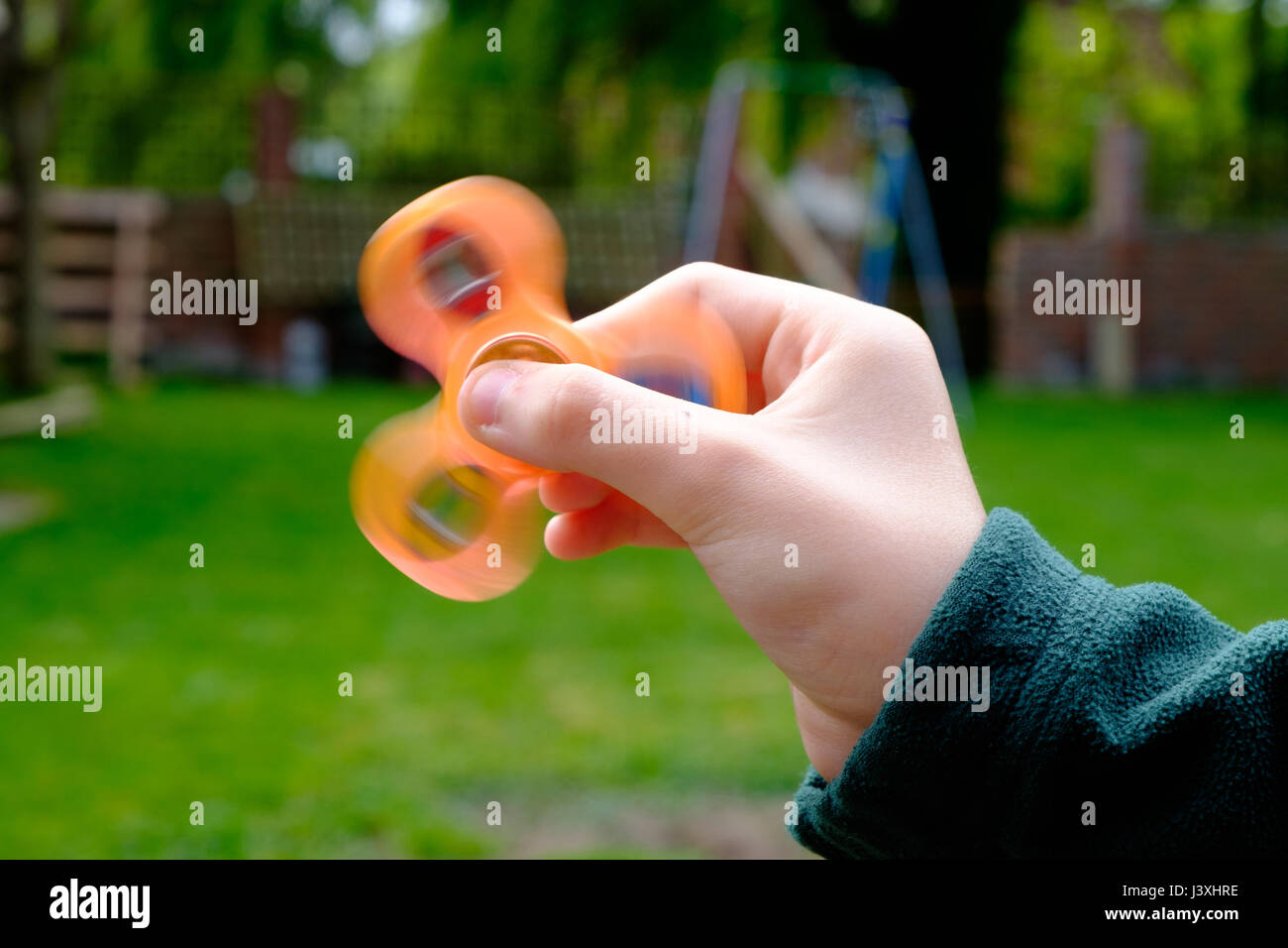 Young boy holding an orange fidget spinner, the latest craze to strike the UK - Stock Image