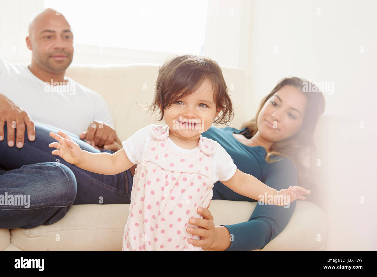 Mother on sofa giving baby daughter helping hand while toddling - Stock Image