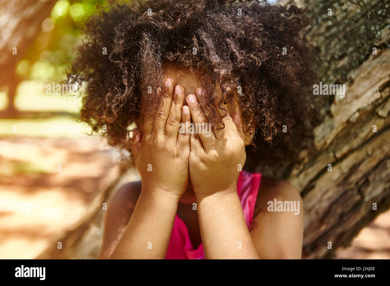 Young girl standing outdoors, covering face with hands - Stock Image