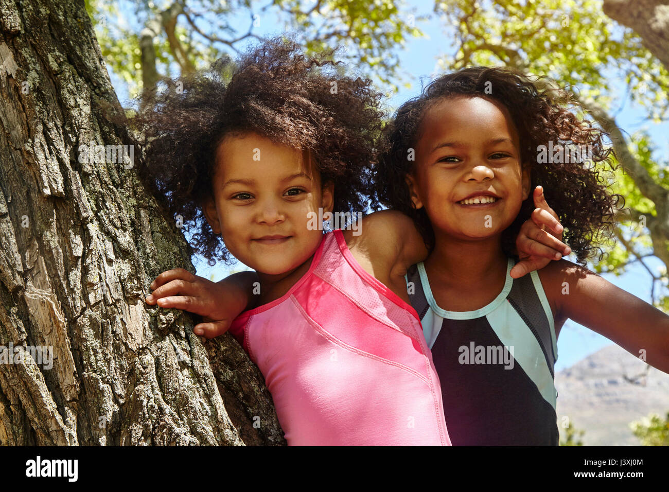 Portrait of two young sisters, climbing tree - Stock Image