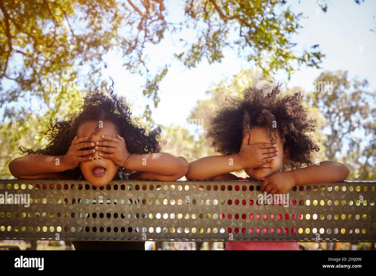 Portrait of two young sisters leaning against fence, covering eyes - Stock Image