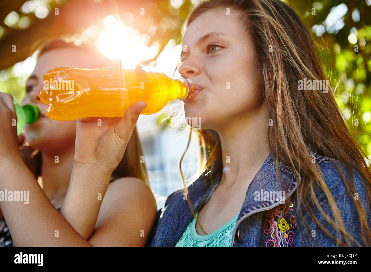 Two female friends sitting outdoors, drinking soft drinks Stock Photo