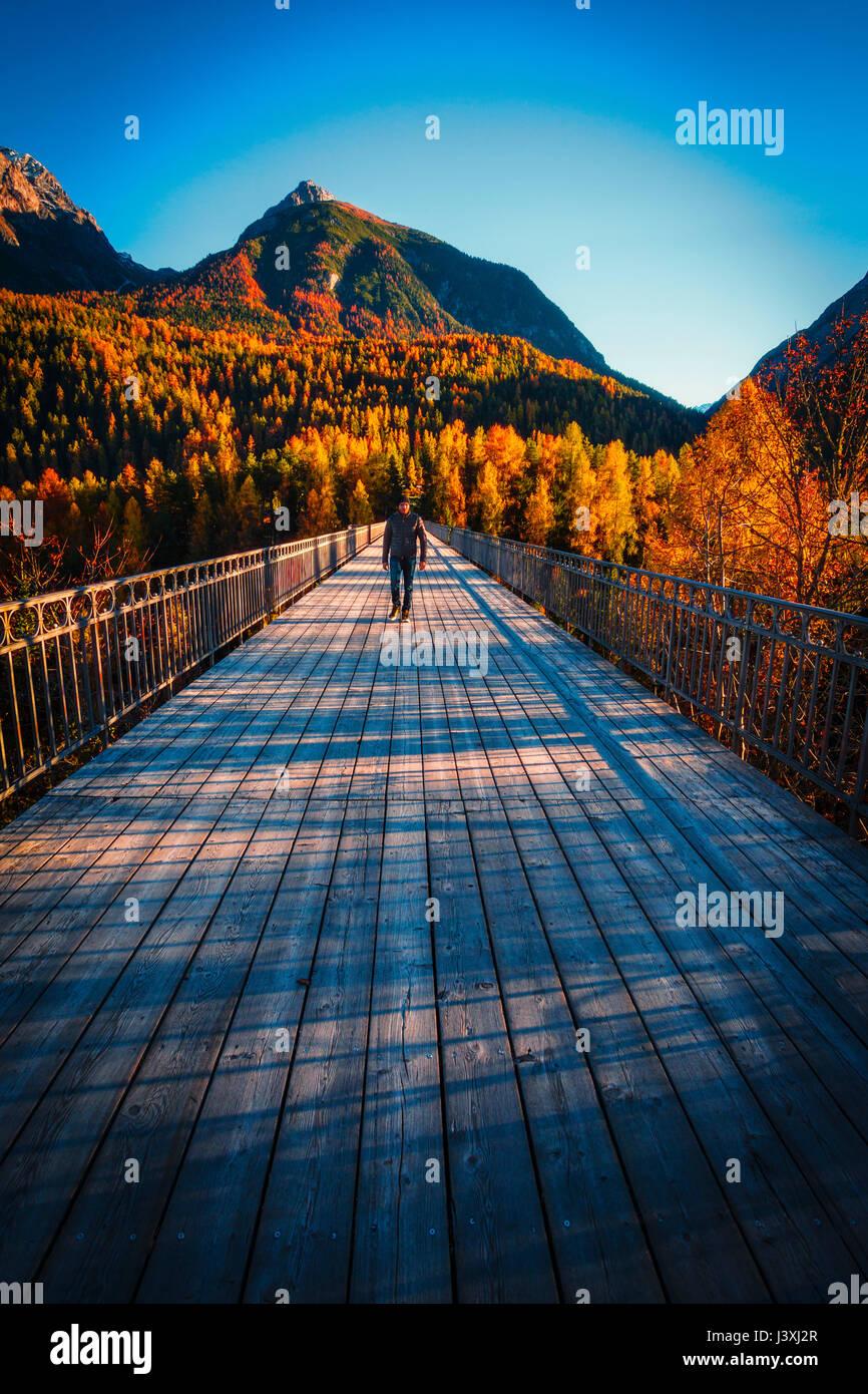 Man walking across wooden bridge, Scuol, Engadin,  Switzerland - Stock Image