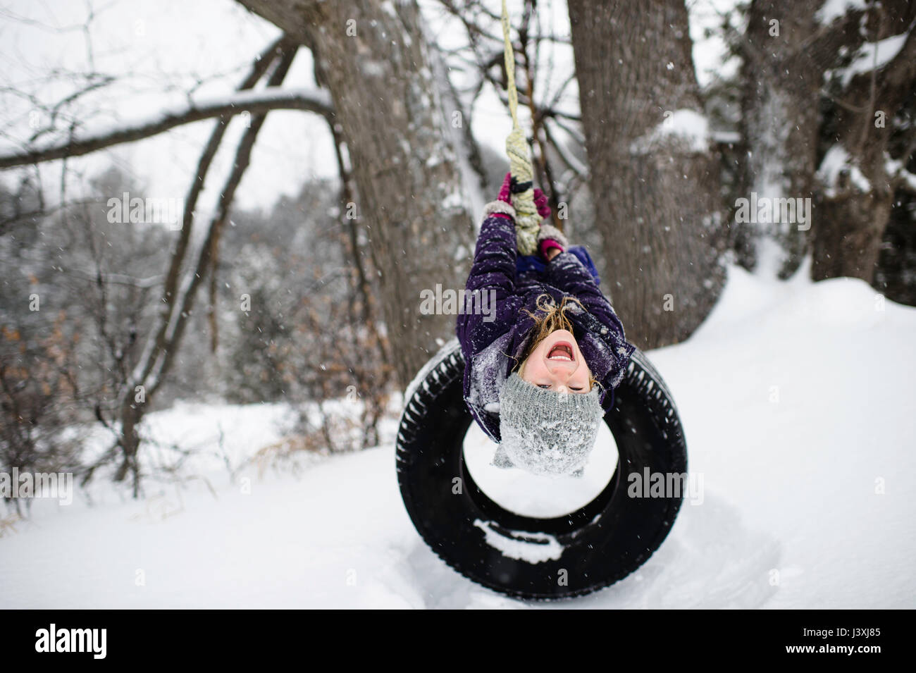 Girl upside down on tire swing in snow - Stock Image