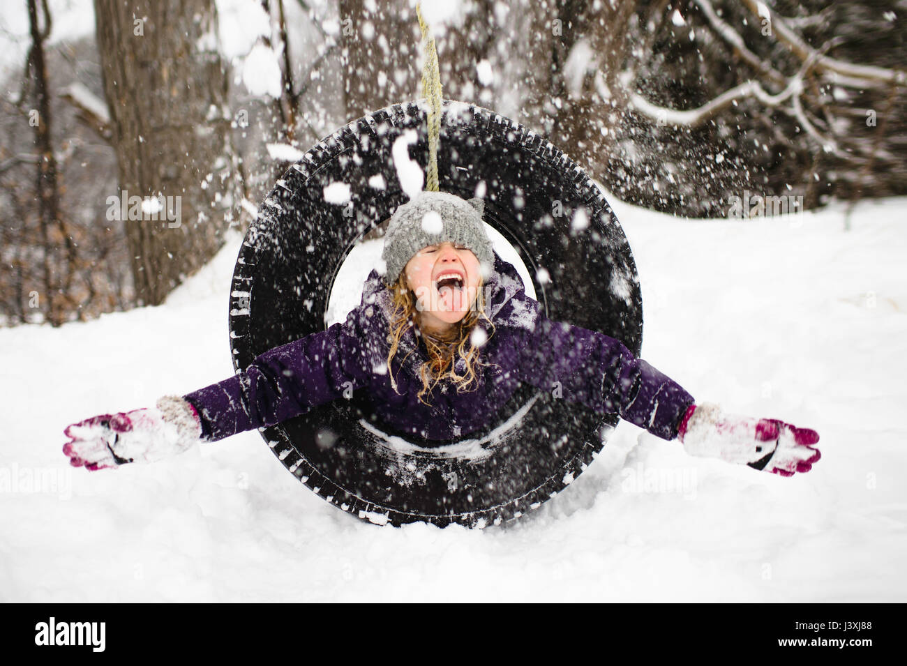 Girl playing in snow on tire swing - Stock Image