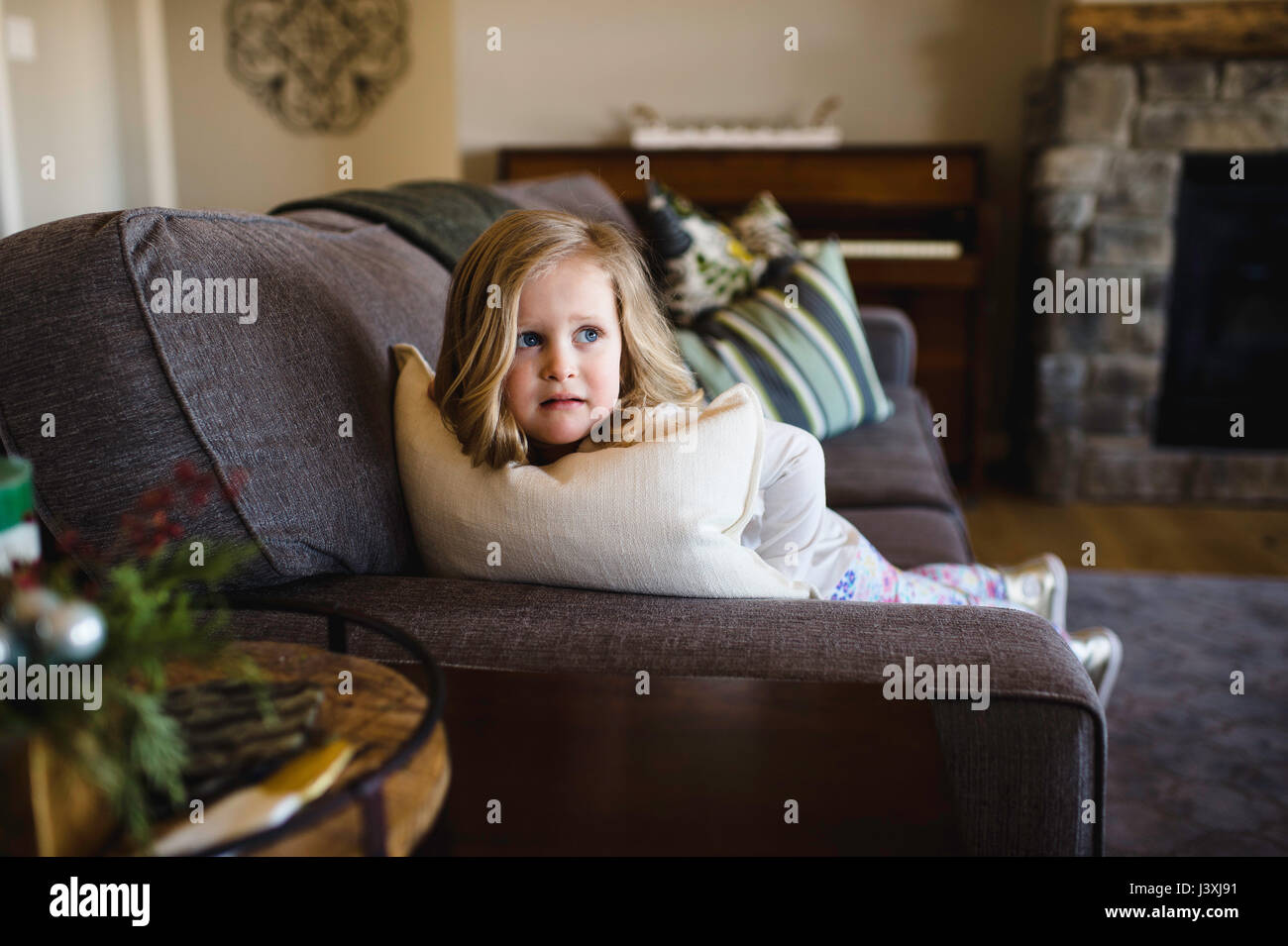 Fearful girl looking sideways from sofa Stock Photo