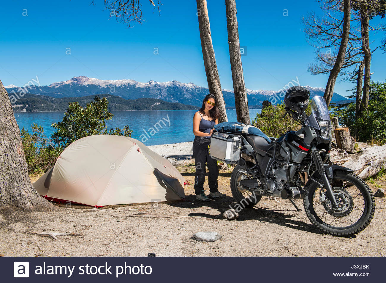 Woman packing touring motorbike at campsite, Nahuel Huapi Lake in Patagonia - Stock Image