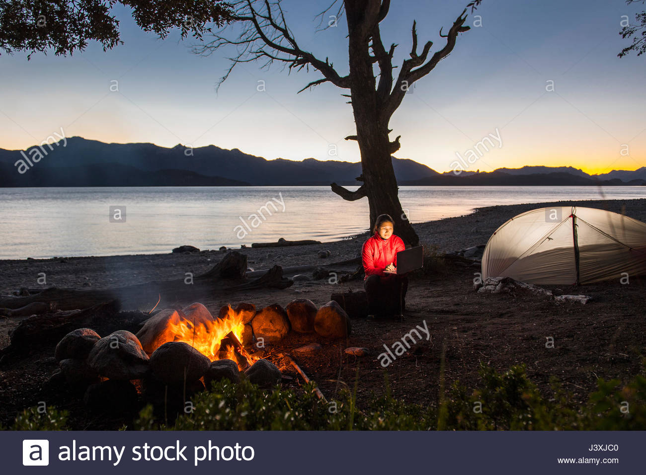 Woman looking at her laptop by a campfire at Nahuel Huapi Lake in Patagonia - Stock Image