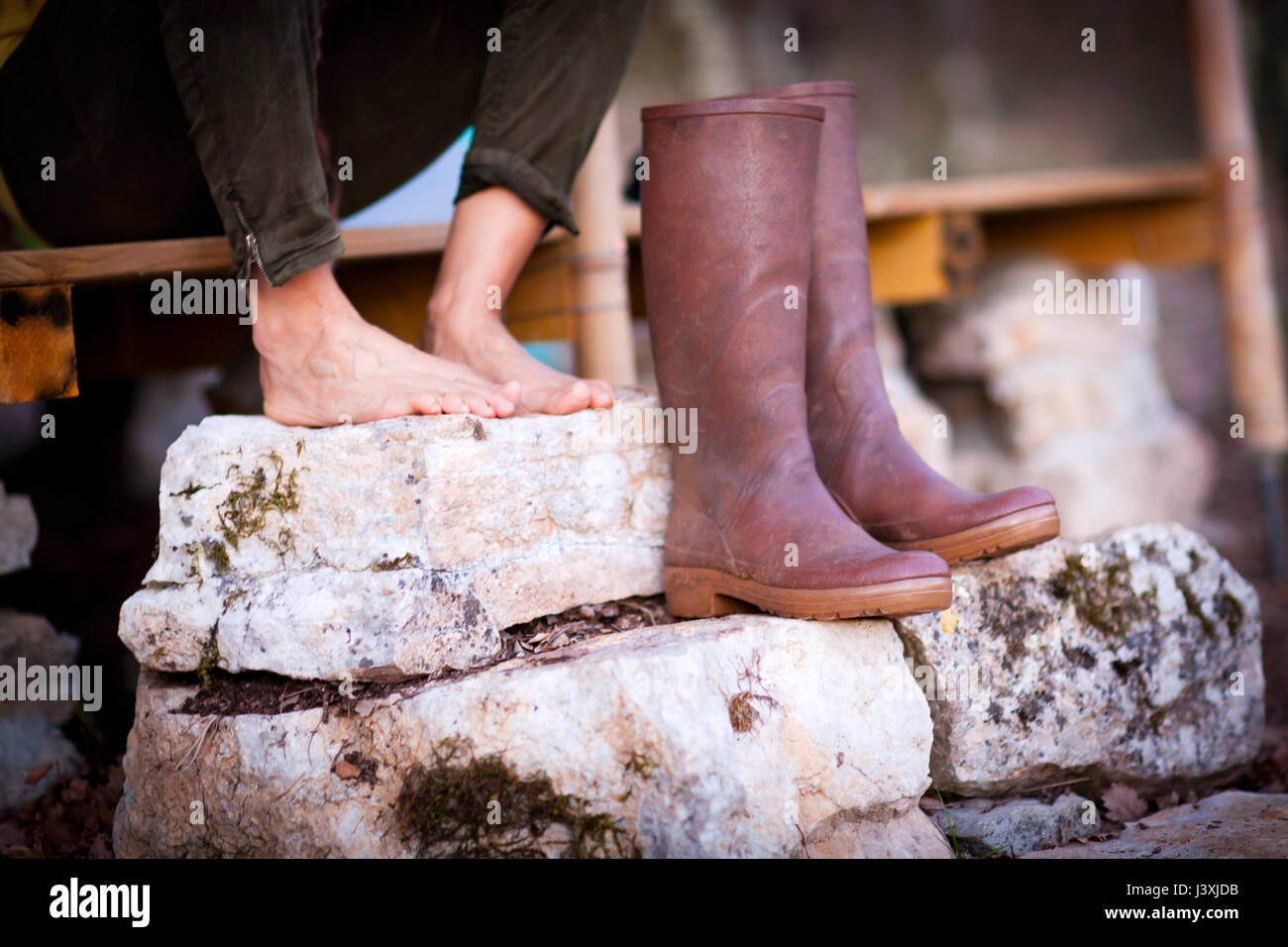 mature woman's bare feet and knee high boots on stone porch steps
