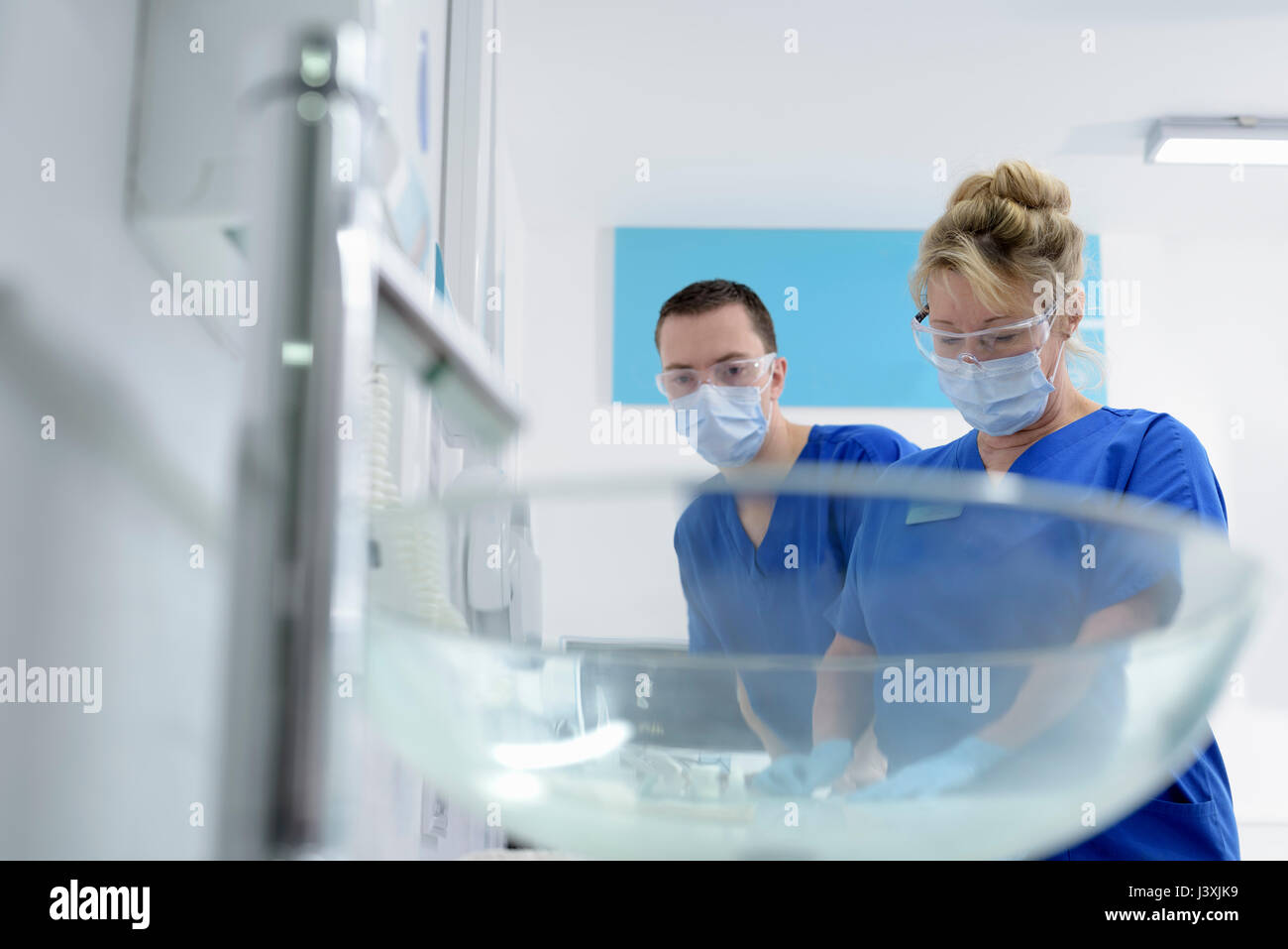 Dentist and assistant nurse in dental surgery - Stock Image