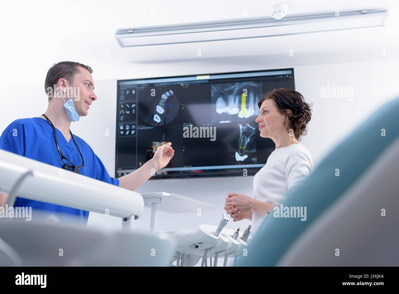 Dentist showing x-rays on screen to patient in dental surgery - Stock Image