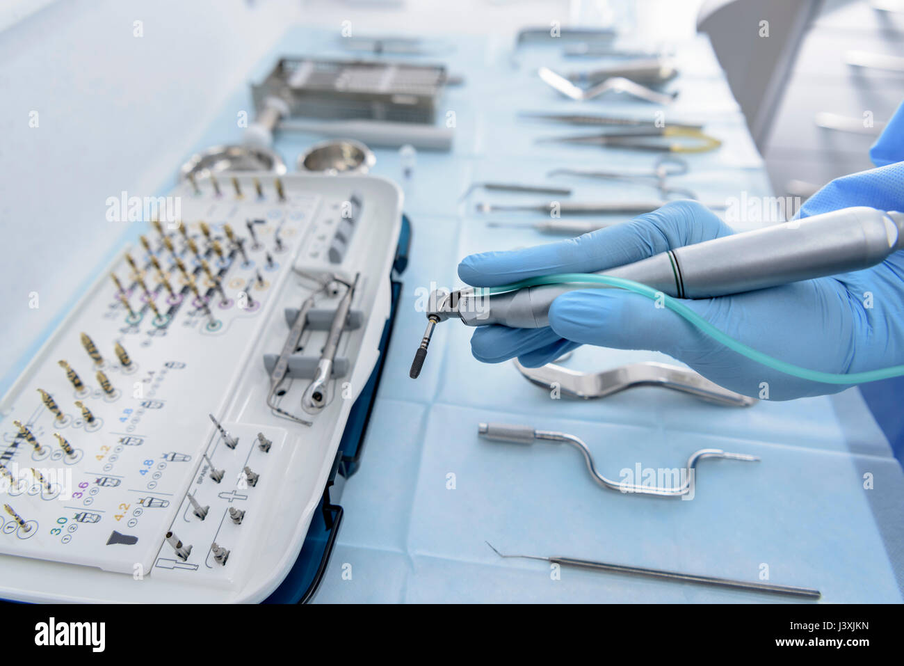 Dentist holding drill in dental surgery, close up - Stock Image