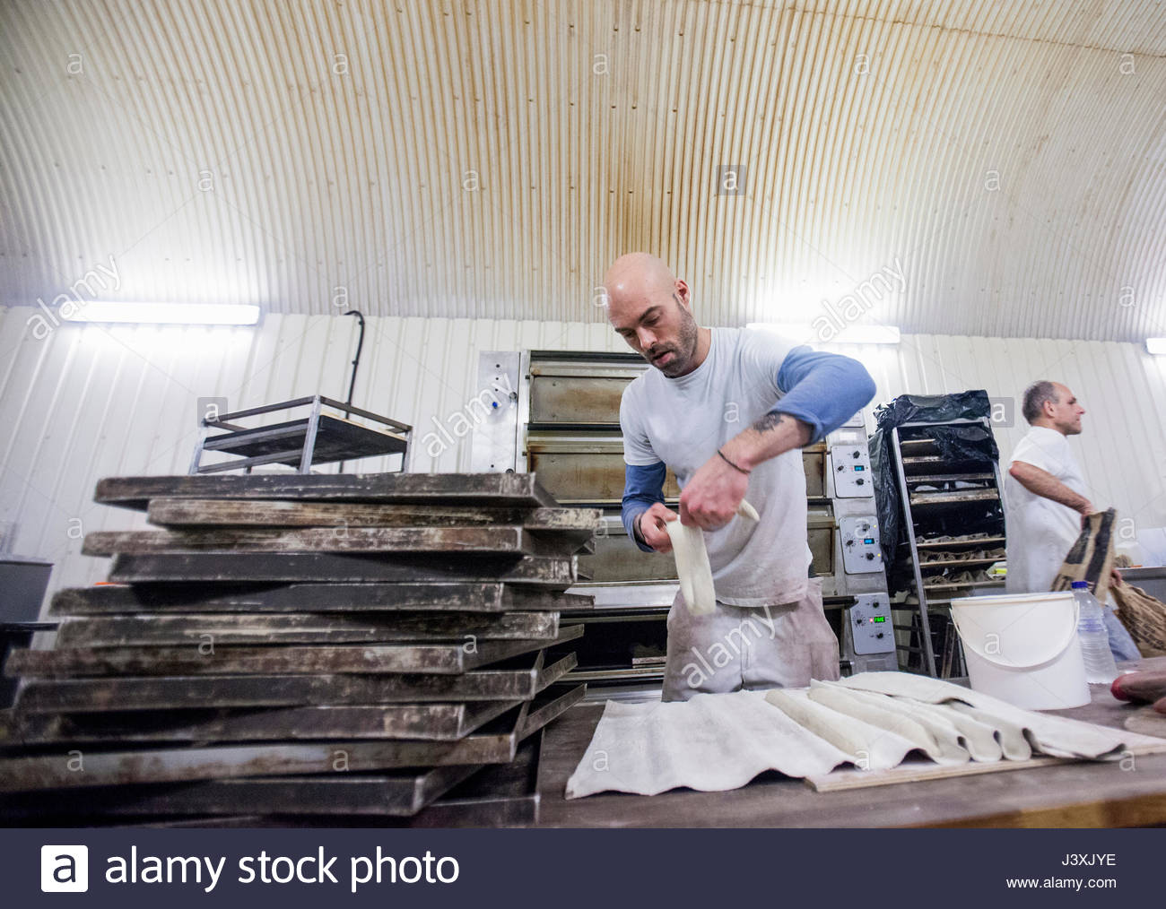 Baker working with dough in bakery - Stock Image