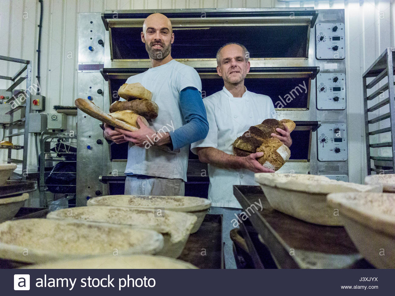 Bakers holding freshly-made bread Stock Photo
