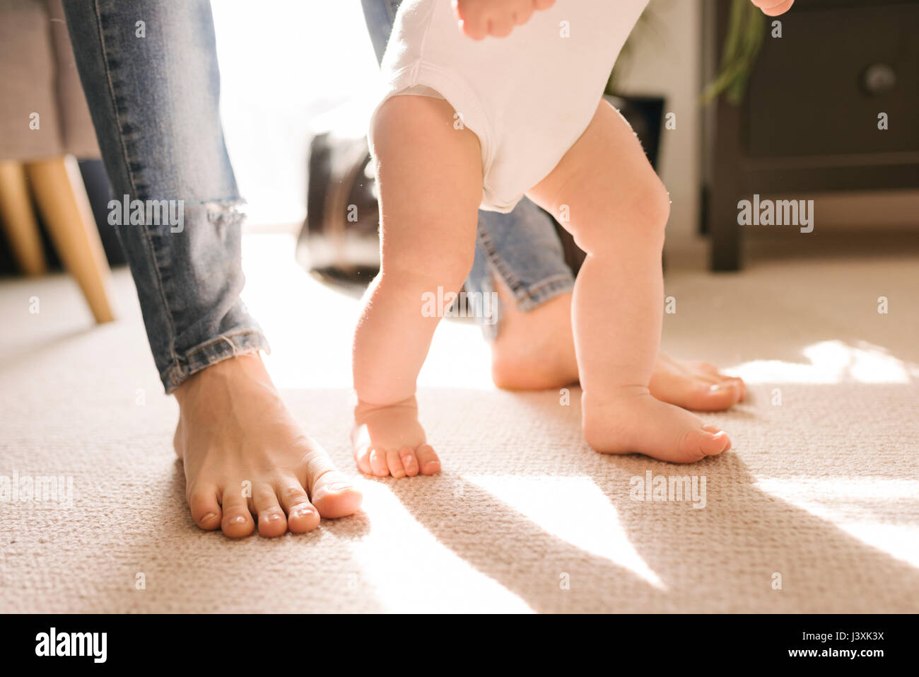 Mother and baby's bare feet on carpet in living room Stock Photo
