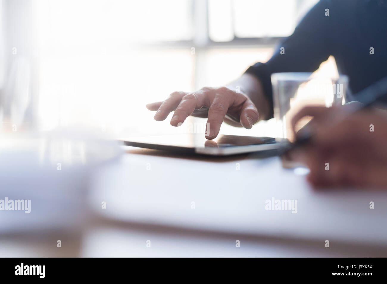 Man using digital tablet on desk, close up of hand - Stock Image