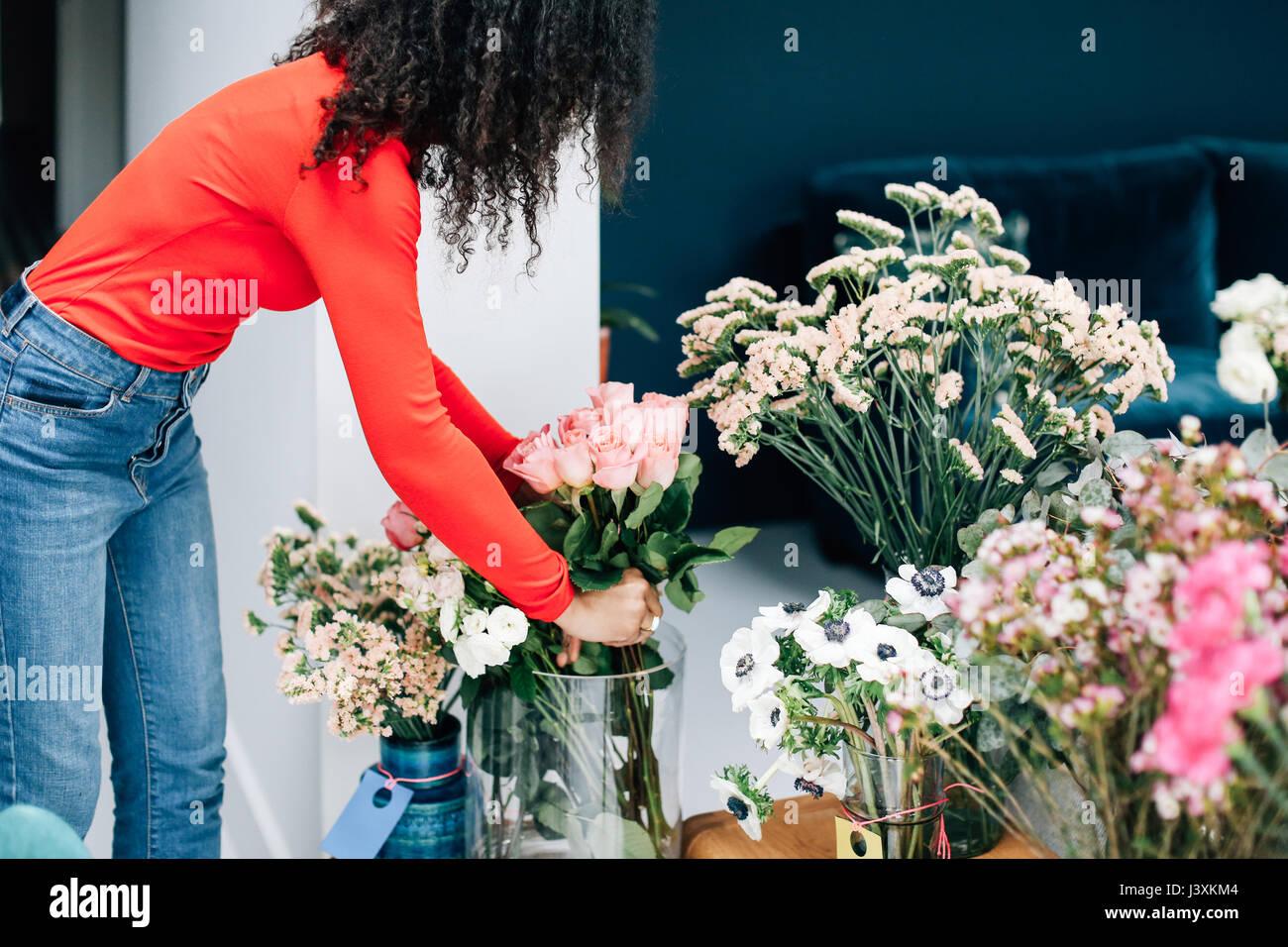 Female florist arranging roses in vase for shop display - Stock Image