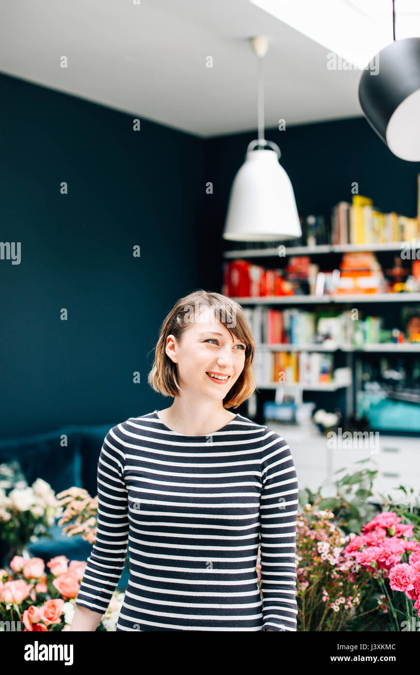 Portrait of female student florist at flower arranging workshop - Stock Image