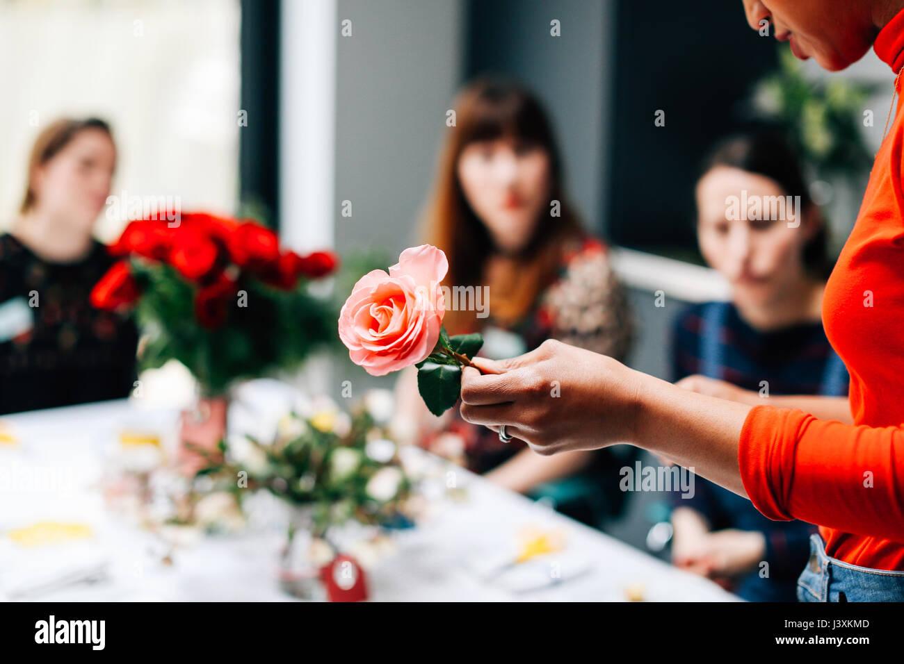 Florist showing rose to students in flower arranging workshop - Stock Image