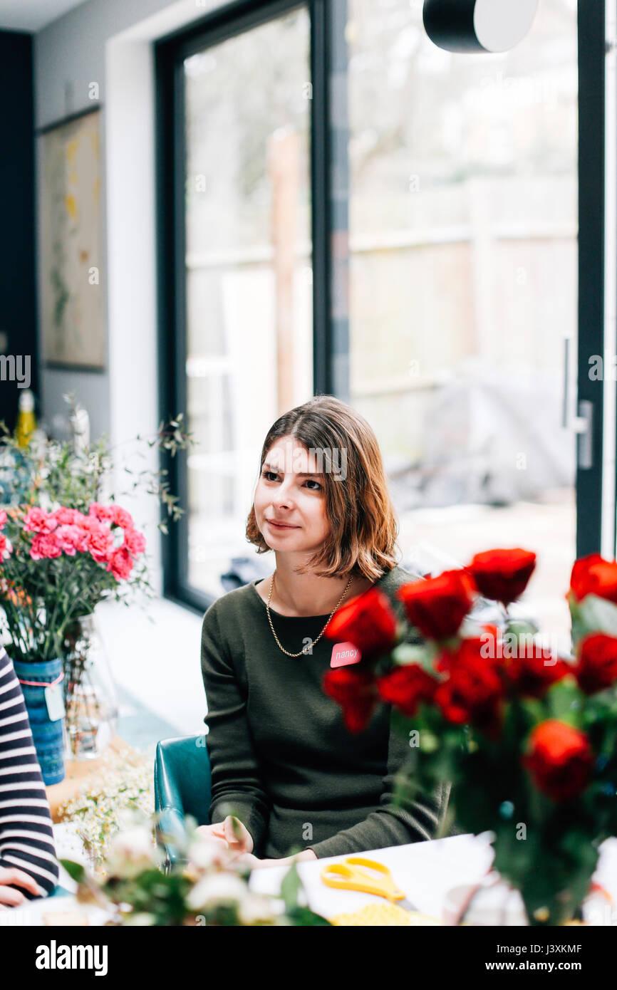 Female student florist listening at flower arranging workshop - Stock Image