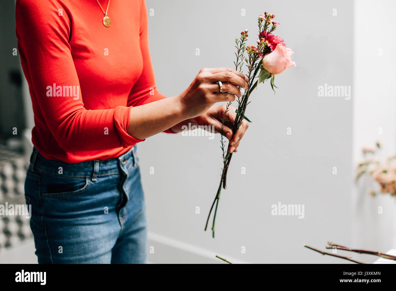 Mid section of female florist holding cut flowers in florists workshop - Stock Image
