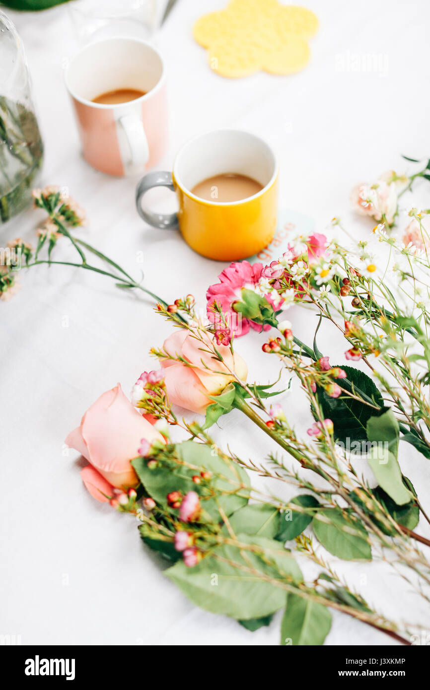 Table with cut flowers and coffee cups at flower arranging workshop - Stock Image