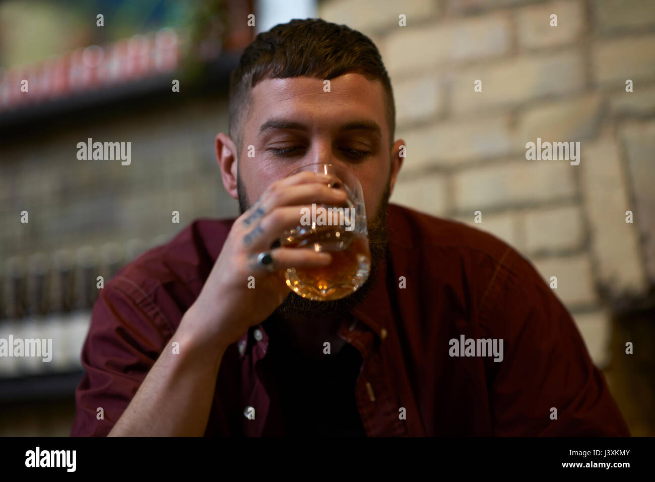Young man with tattooed fingers drinking tumbler of spirit in public house Stock Photo