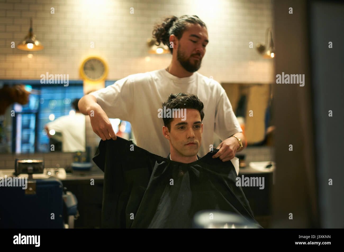 Barber putting gown onto male customer in barber shop - Stock Image