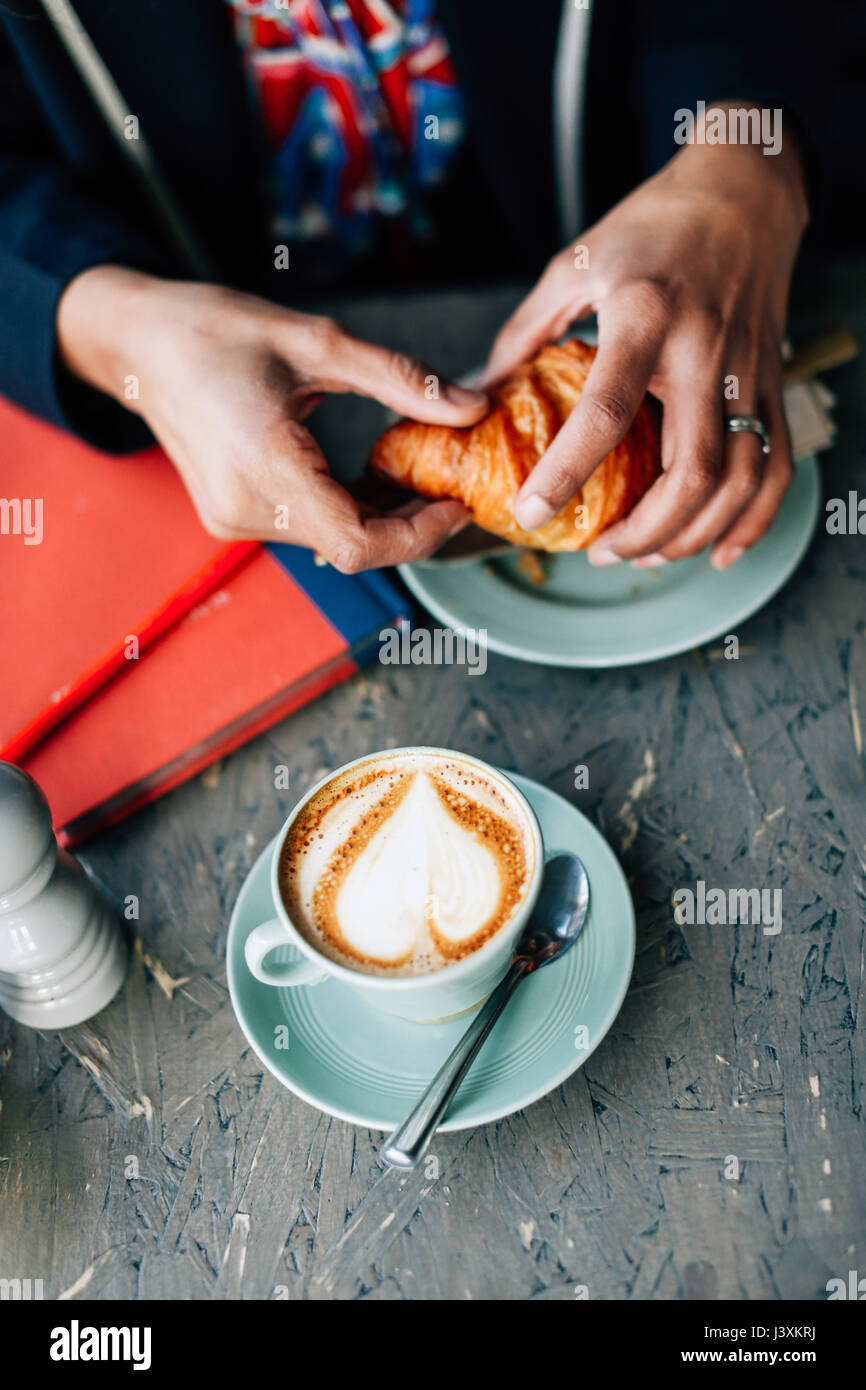 Overhead view of woman's hand holding croissant in cafe - Stock Image