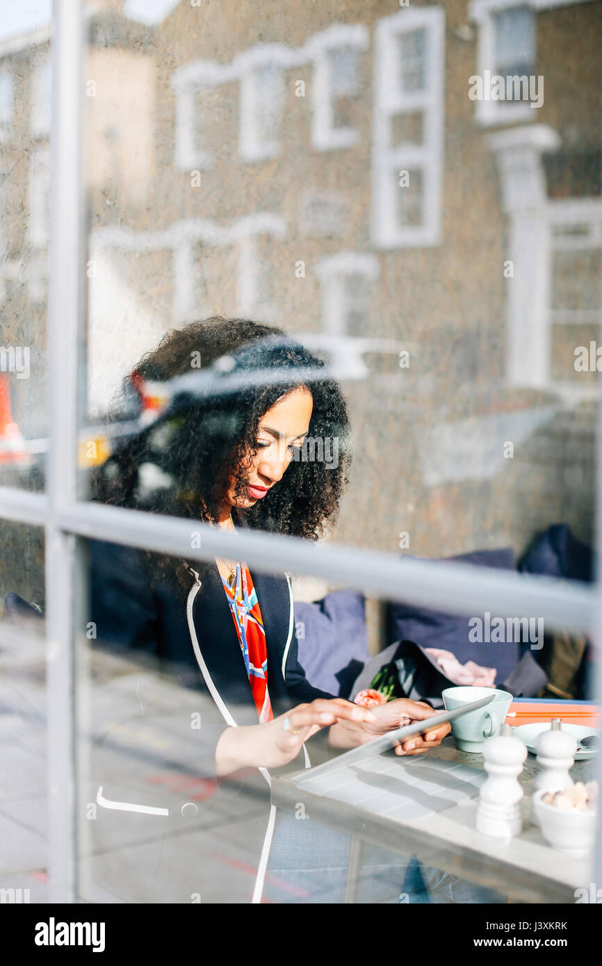 Window view of woman using digital tablet in cafe - Stock Image