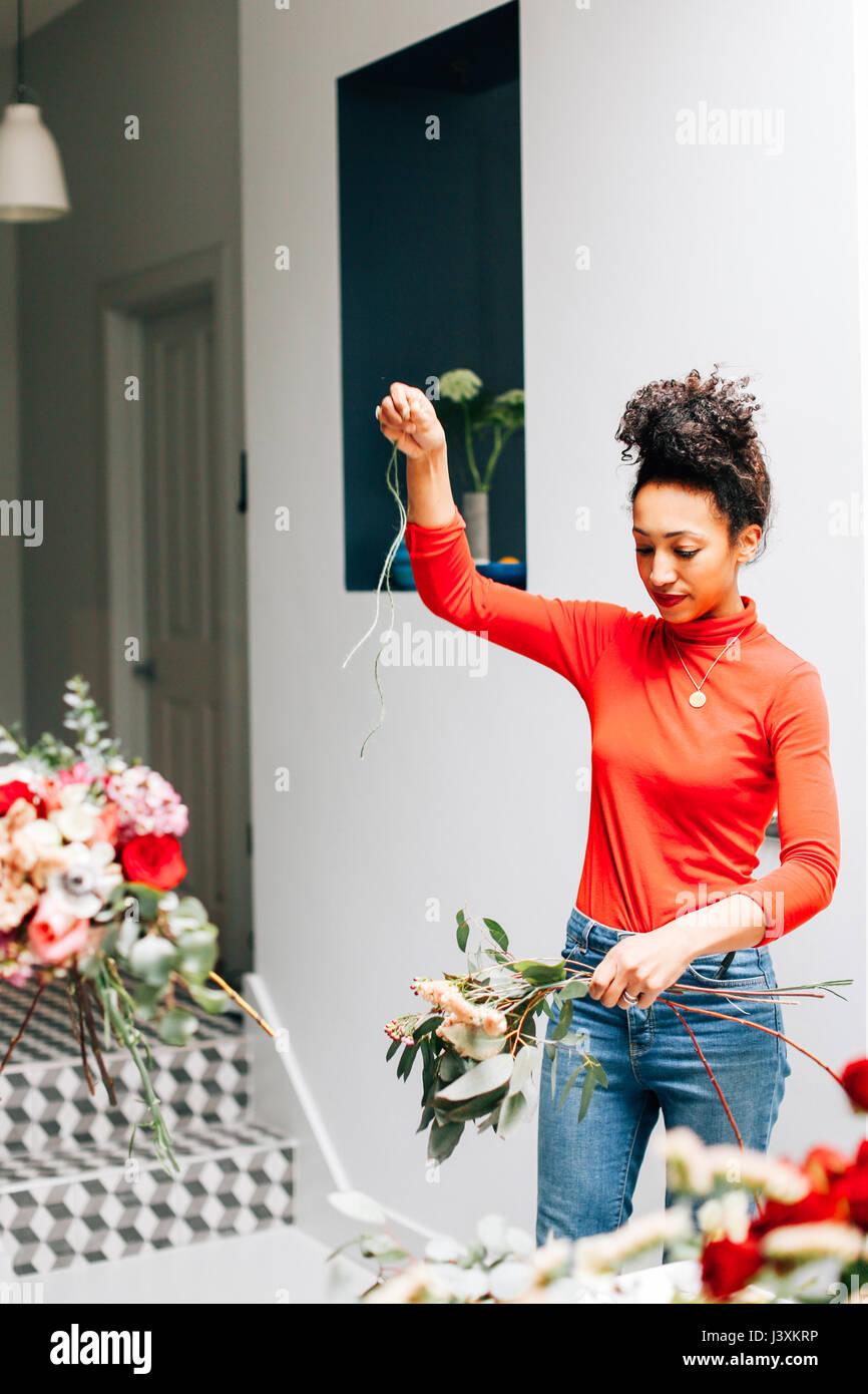 Female florist tying cut flowers in florists workshop - Stock Image