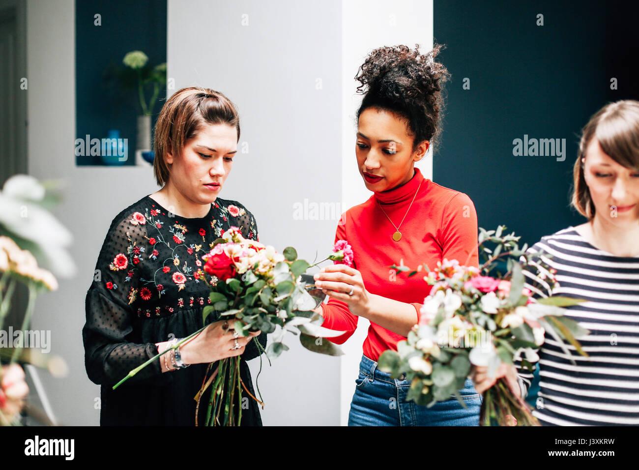 Florist students arranging bouquets at flower arranging workshop - Stock Image